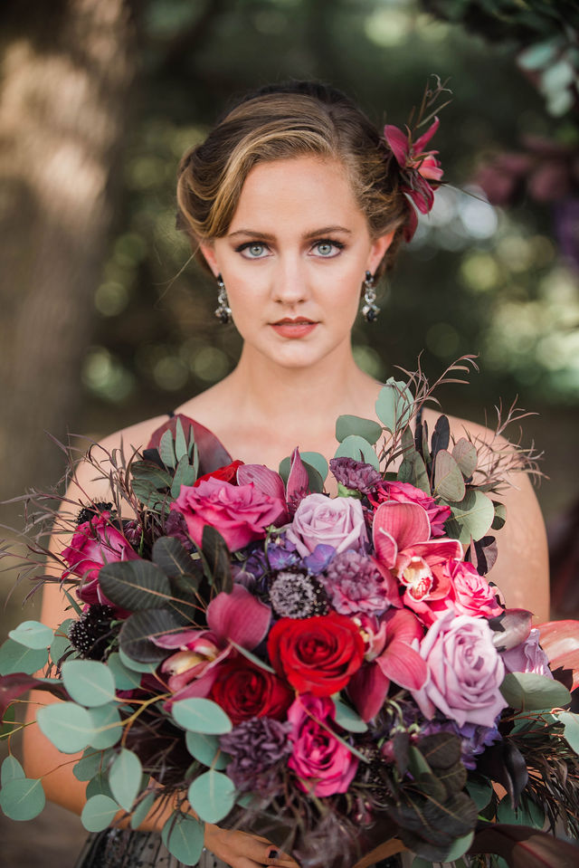 Beautiful bride holding a burgundy and lavender rose bouquest designed by Dream Bouquet